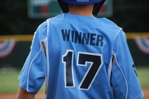 Child wearing a baseball jersey with the name winner on the back and the number 17